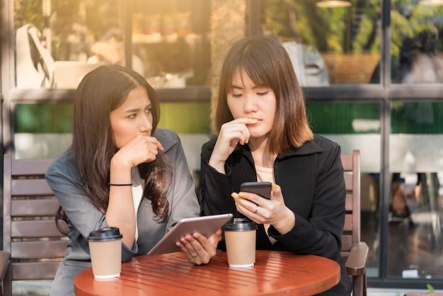 アジアの美しいビジネス女性のコーヒーカフェショップでタブレットとスマートフォンの操作 Premium写真