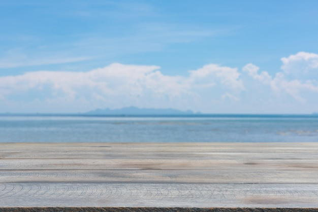 ぼやけた青い海空の背景を持つ板木テーブルトップ Premium写真