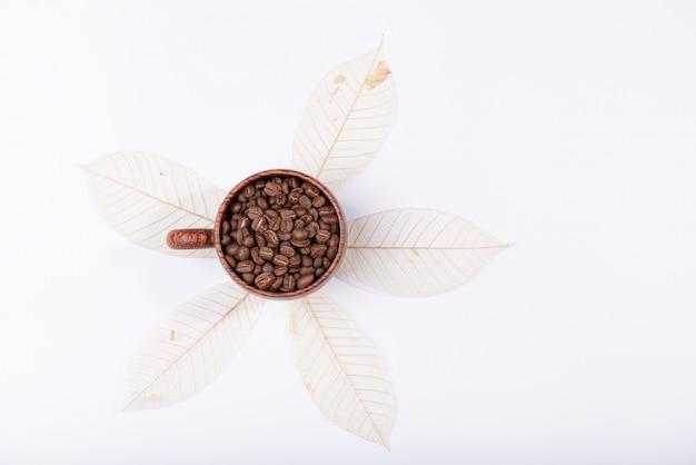 Жареные кофейные зерна в деревянной чашке над высушенным листом Premium Фотографии