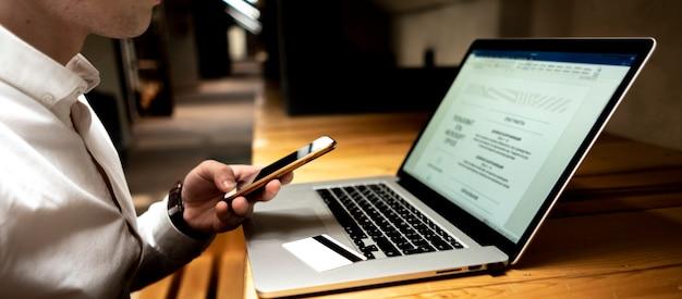 電話、ノートパソコン、彼の職場で電子決済を行うカードを持ったビジネスマン Premium写真