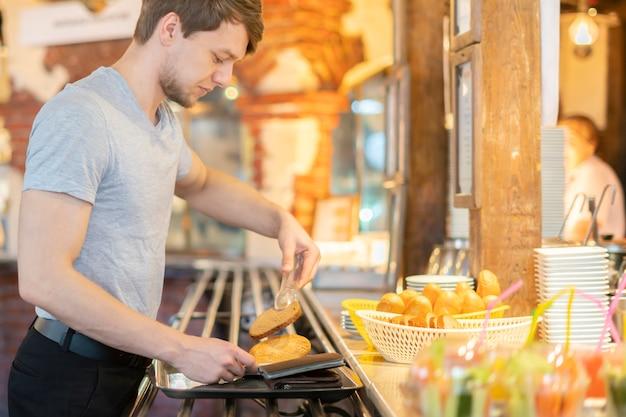若い男の側面図はストリートカフェで朝食の食材を選ぶ Premium写真