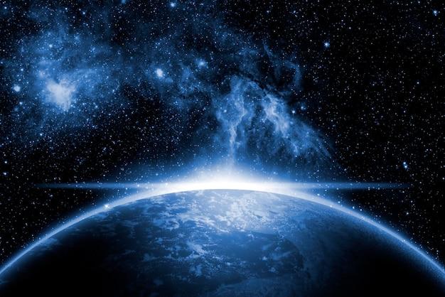 創造的な宇宙アート。日の出と太陽フレアのある地球。 Premium写真