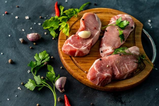 木製のスライスやまな板の上のスパイシーな生肉、未調理の肉に塩を入れる Premium写真