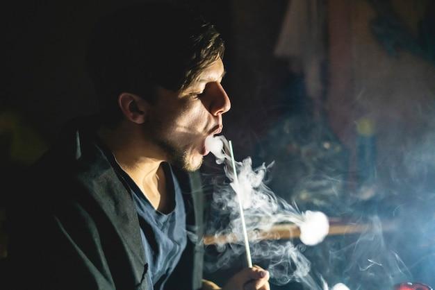 若い男が暗い部屋でアジアの水ギセルを吸う、リラックスして休憩 Premium写真