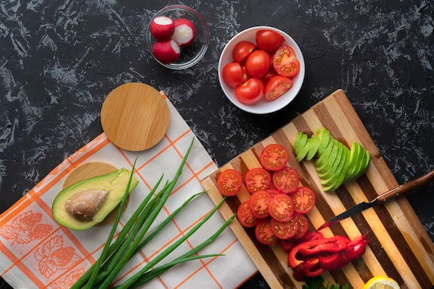 まな板、トマト、アボカド、ピーマンの新鮮な有機フラットレイアウトスライス野菜を閉じる Premium写真