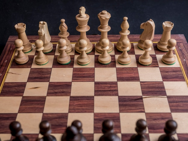 黒いテーブルの上のデフォルトの位置のチェスボードゲームを閉じる Premium写真