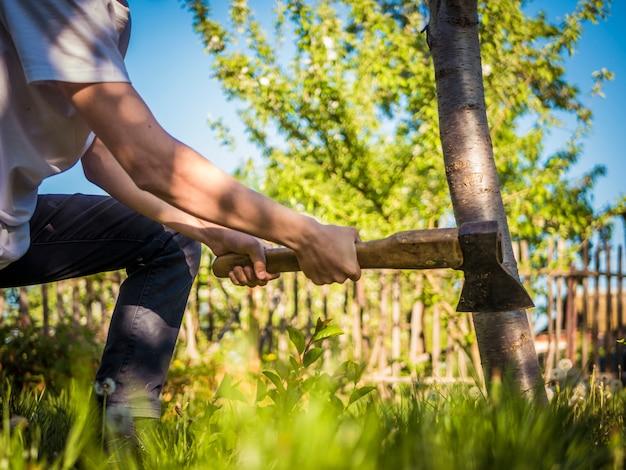 庭で働く男の手に斧のショットを閉じる Premium写真