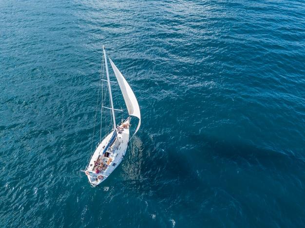 まだ海空中平面図で行く背の高いマストと帆の下で孤独な孤立したヨット Premium写真
