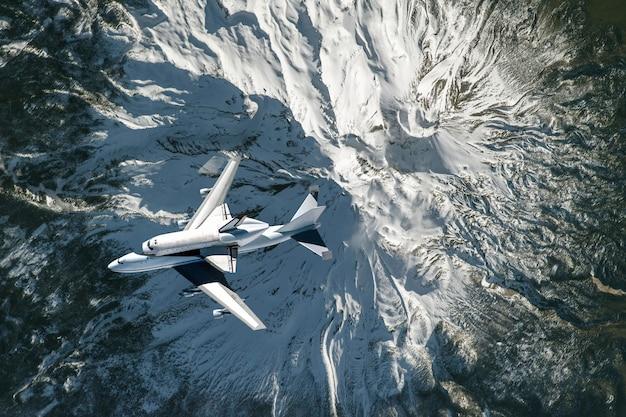 スペースシャトルと飛行機は地球大気の上空で飛ぶ Premium写真