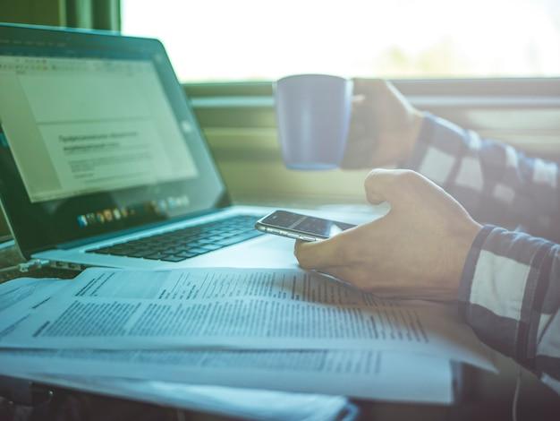 窓の近くの電車の中でノートパソコンと紙を扱うフリーランサー Premium写真
