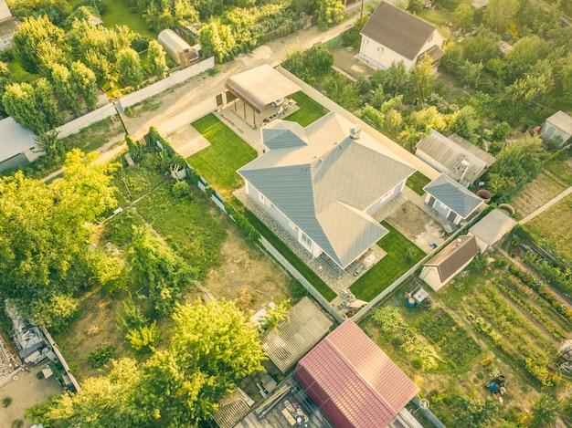 夏の田舎のコテージと庭の空中ドローンショット。 Premium写真