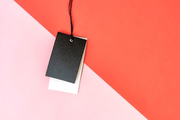赤黄色とピンク色の背景上のコピースペースで孤立した服の価格タグ。 Premium写真