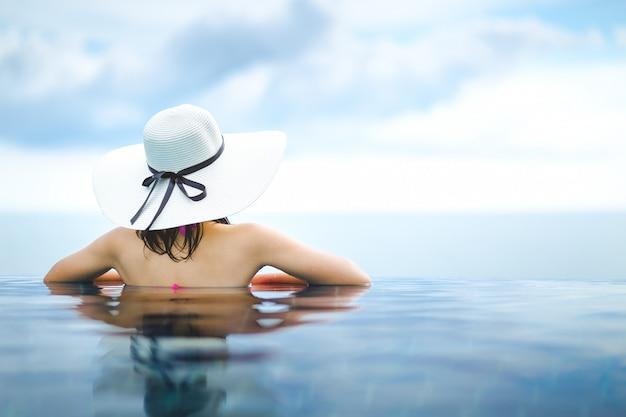 アジアの女性はビーチでプールでリラックスします。 Premium写真