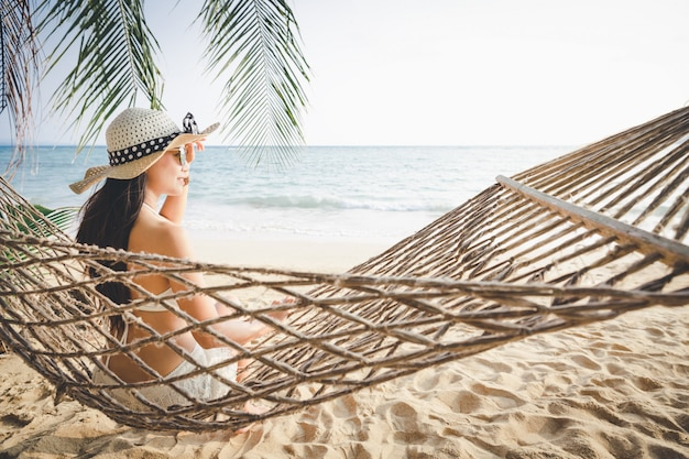 Счастливая женщина расслабиться в гамаке Premium Фотографии