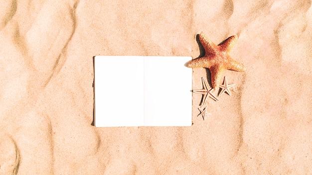 空白のノートブックと砂の背景にヒトデ 無料写真
