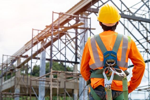 高所で作業する安全ハーネスと安全ラインを身に着けている建設労働者、労働安全衛生の実践は、職場の危険を軽減するために危険管理と介入を使用できます。 Premium写真