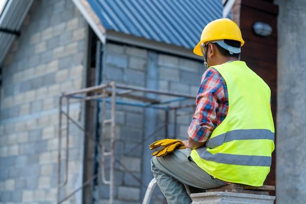 工事現場の建物の屋根構造の作業中に安全ハーネスベルトを着用する屋根葺き職人。 Premium写真