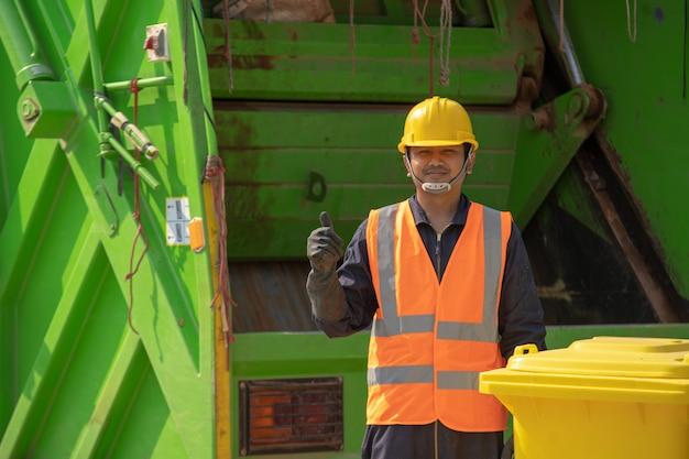 ガベージコレクター、日中通りにゴミ箱を持つ幸せな男性労働者。 Premium写真