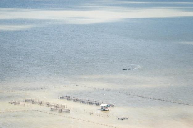 地元の漁船とソンクラー湖の木の浮遊家屋で伝統的な魚のトラップの空撮。タイ。 Premium写真