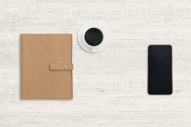 ノートブックと木の上のコーヒーカップを持つスマートフォン。 Premium写真