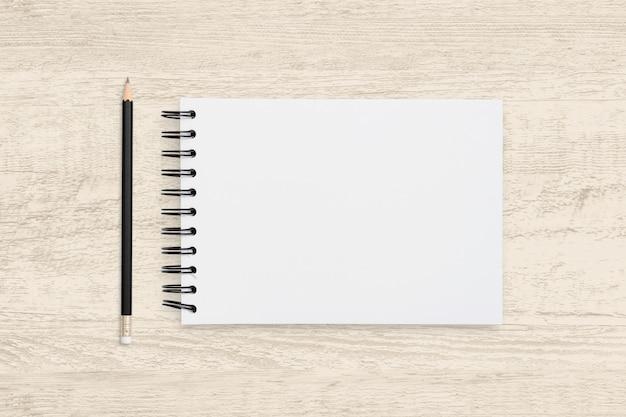 空白のノートブックとウッドテクスチャの鉛筆の平面図オブジェクト。 Premium写真