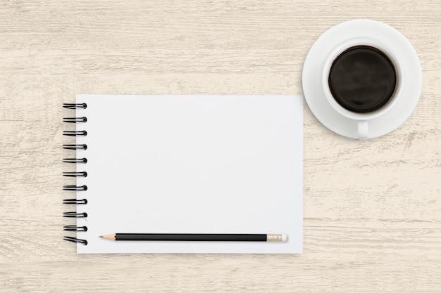 木材の背景にコーヒーカップとノートのホワイトペーパーシートの平面図ビジネス。 Premium写真