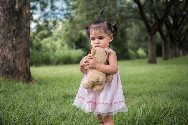 Маленькая девочка одиноко под деревом, одиноко со своей куклой Premium Фотографии