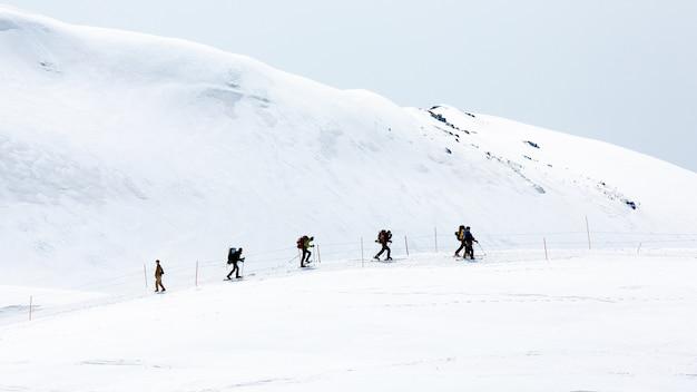 雪に覆われた山脈を歩くスキーヤー Premium写真