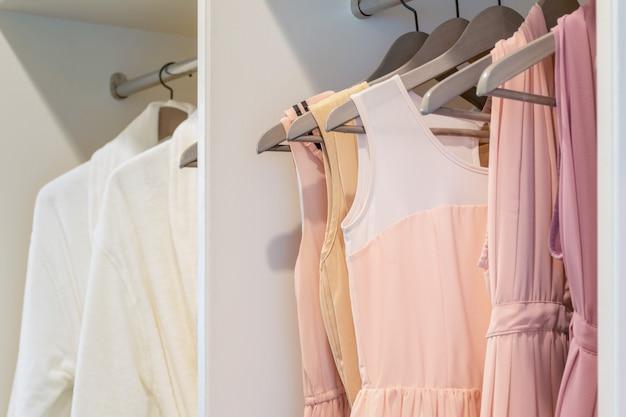 白いワードローブのコートハンガーに掛かるカラフルなドレスの行 Premium写真