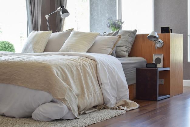 スタイリッシュなベッドルームインテリアデザイン。ベッドに白い縞模様の枕と装飾的なテーブルランプが付いています。 Premium写真