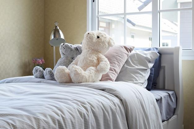ベッドとベッドサイドテーブルランプに人形と枕が置かれた子供用の部屋 Premium写真