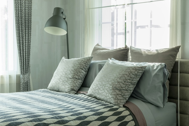 ベッドに装飾された枕と装飾的なテーブルランプを備えたスタイリッシュなベッドルームインテリアデザイン。 Premium写真