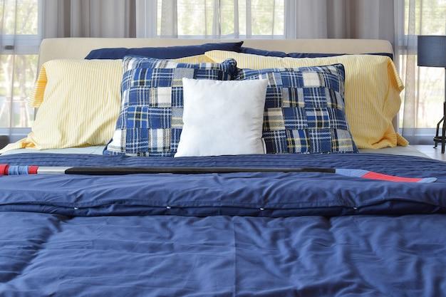 ベッドに青い模様の枕が付いたスタイリッシュなベッドルームインテリアデザイン Premium写真