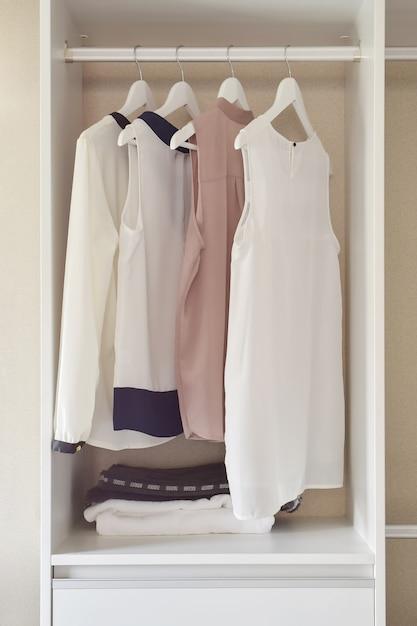 白いワードローブのコートハンガーに掛かっているドレスの行 Premium写真