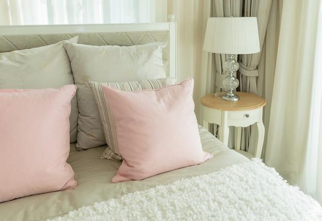 ピンクの枕とベッドサイドテーブルの上の読書ランプ付きの居心地の良いベッドルームのインテリア Premium写真