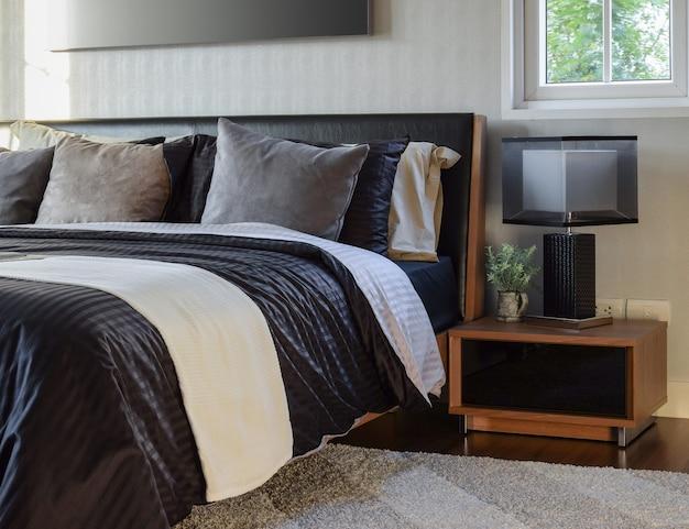 モダンなベッドサイドテーブルランプで装飾的なスタイリッシュなベッドルームのインテリア Premium写真