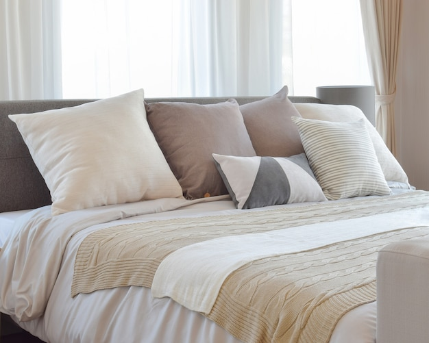 ベッドと装飾的なテーブルランプの上の茶色の模様入り枕とスタイリッシュなベッドルームのインテリアデザイン。 Premium写真