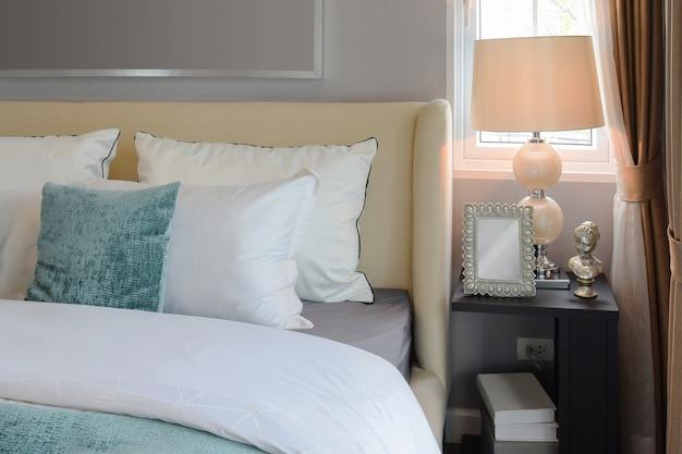白いベッドと装飾的なテーブルランプの上の白と緑の枕の寝室のインテリアデザイン。 Premium写真