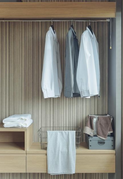 Рубашки висят в деревянном гардеробе Premium Фотографии