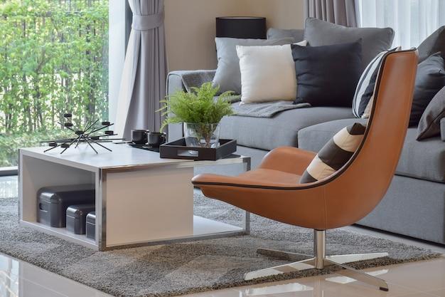 花瓶の植物とモダンな革張りの椅子に黒の模様の枕のあるリビングルーム Premium写真