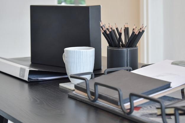 Рабочий стол с книгой, карандашами, чашкой кофе и часами в доме Premium Фотографии