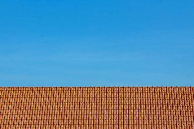 オレンジ色の屋根瓦と青空の背景 Premium写真