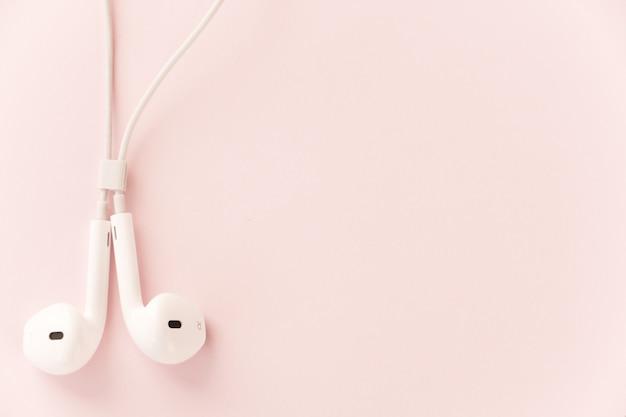 甘いパステル調の背景に白いヘッドフォン Premium写真