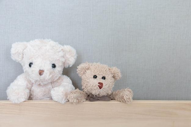 テディベアのカップルは灰色の木板にあります。 Premium写真