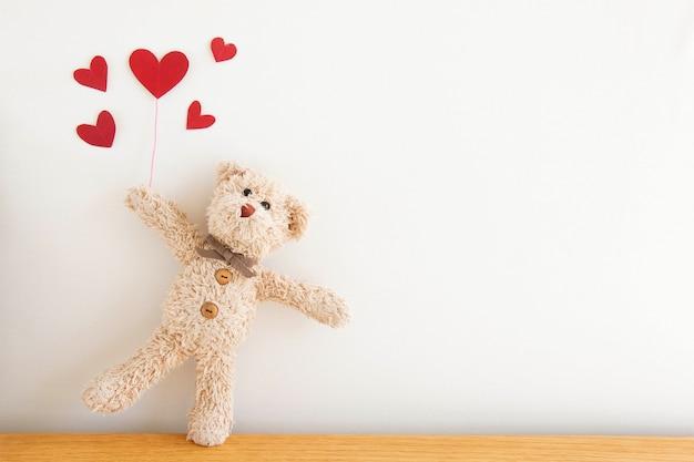 赤いハートの風船でかわいいテディベア、彼は幸せと笑顔、幸せなバレンタインデーのコンセプトです。 Premium写真