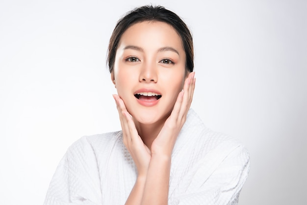 清潔で新鮮な肌と柔らかい頬と笑顔に触れる美しい若いアジア女性。幸福と陽気で、白で隔離、美容と化粧品、 Premium写真
