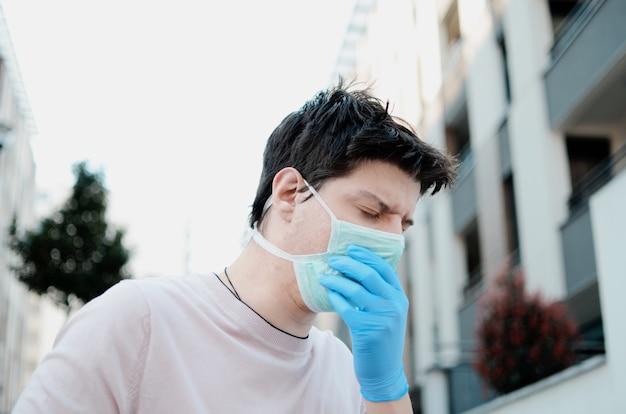 Человек кашляет в защитной маске на улице, с аллергией загрязнения воздуха и боли в легких. молодой человек с защитной маской и перчатки на открытом воздухе Premium Фотографии