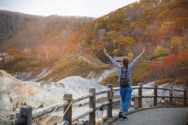 日本から撮影した、秋の通りと赤黄色のカエデの木の上を歩く女性。 Premium写真