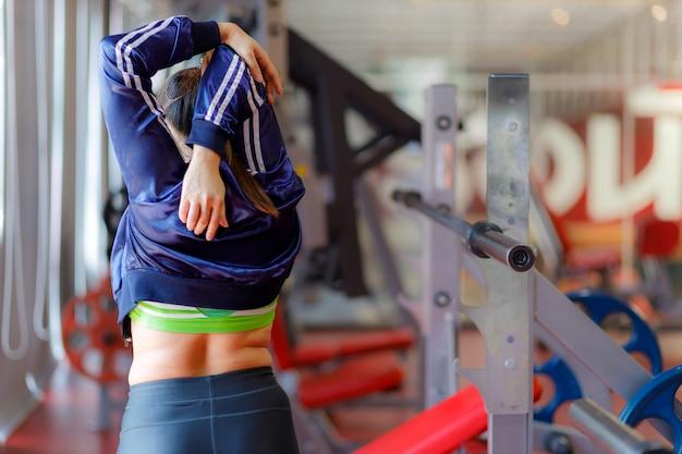 運動している太った女性。フィットネスと運動の前にジムで運動している若いフィットネス女性。 Premium写真