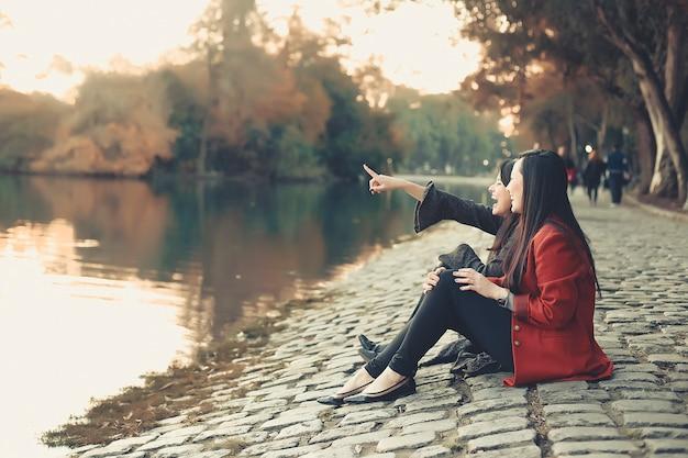 Девушки и подруги сидят в парке Premium Фотографии